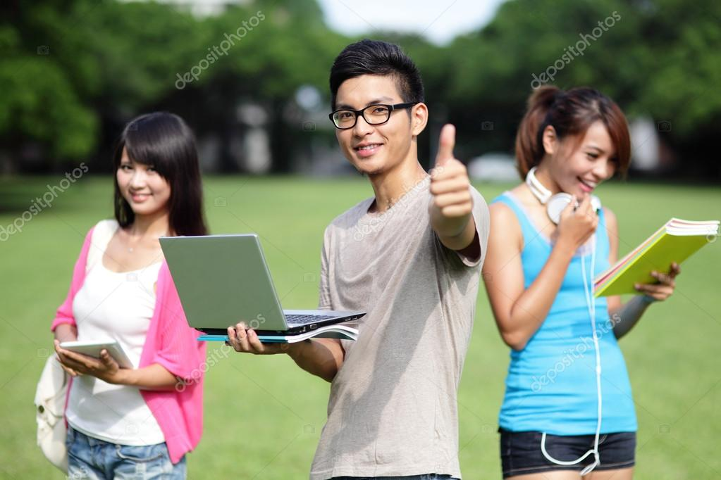 A photo of three students who are extremely happy. The student in the middle is giving a thumbs up.